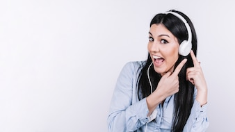Excited woman pointing at headphones