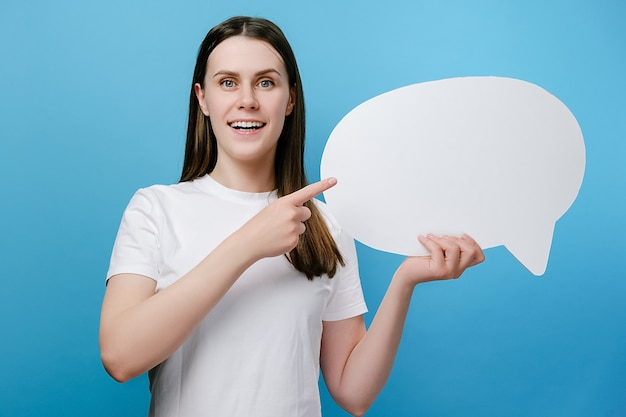 Excited woman pointing at blank speech bubble