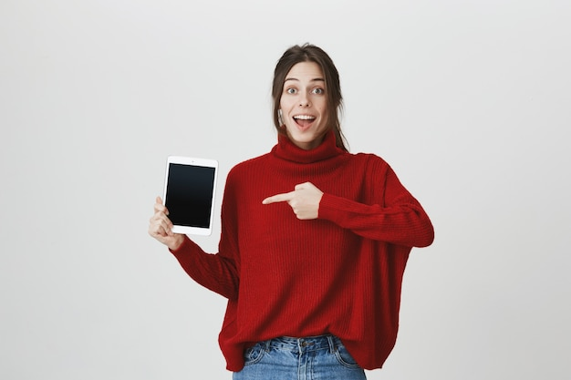 Взволнованная женщина, указывая пальцем на экран цифрового планшета