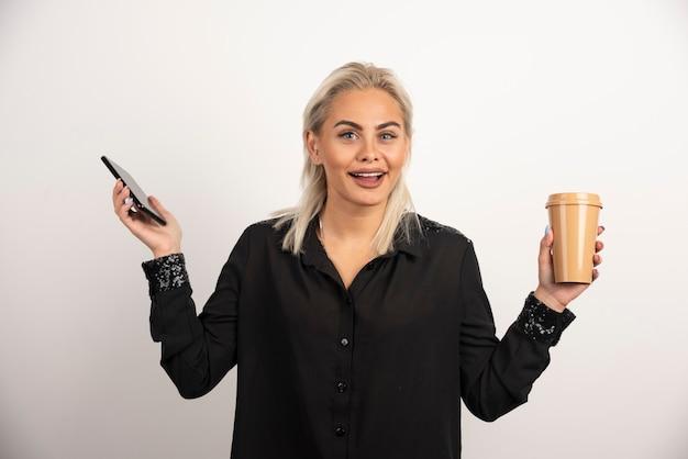 携帯電話と一杯のコーヒーでポーズをとる興奮した女性。高品質の写真