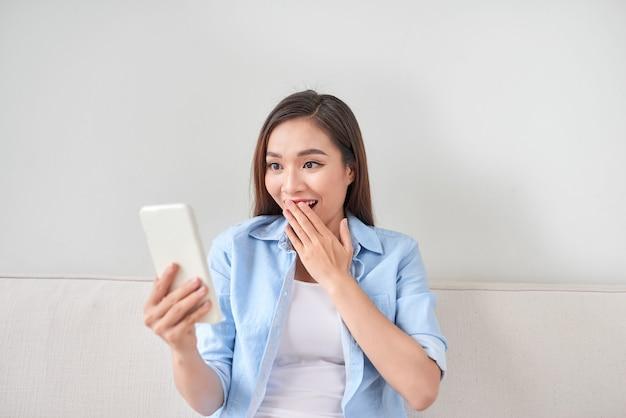 집 거실에 있는 소파에 누워 전화로 문자를 읽는 흥분된 여성