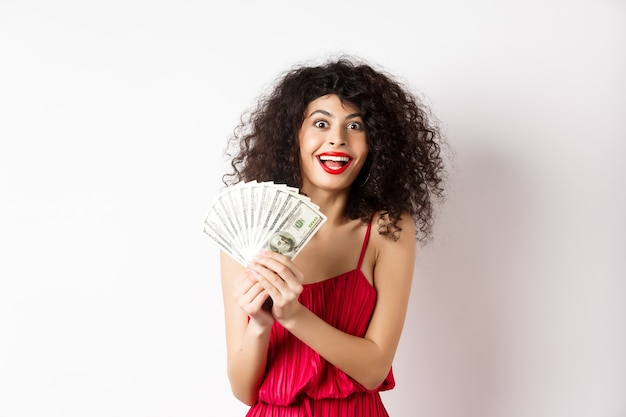 Excited woman in red dress winning money, showing dollar bills and smiling happy, standing on white background.