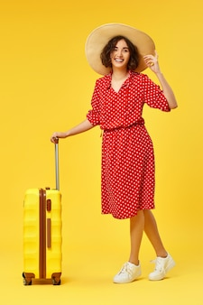 Excited woman in red dress with suitcase going traveling on yellow background.
