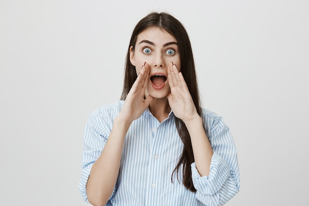 Excited woman shouting with hands over opened mouth