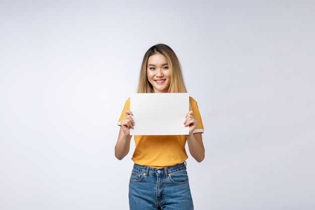 Excited woman showing empty blank paper card sign with copy space for text