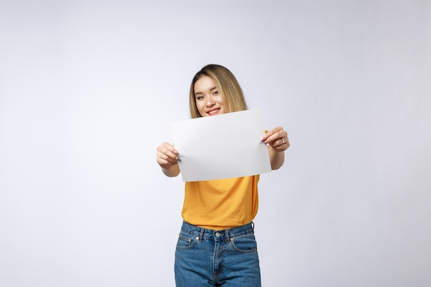 Excited woman showing empty blank paper card sign
