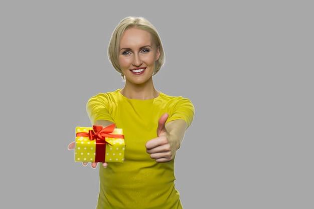 선물 상자와 엄지 손가락을 보여주는 흥분된 여자. 회색 배경에 작은 선물 상자 및 승인 기호를 보여주는 행복 한 웃는 여자.
