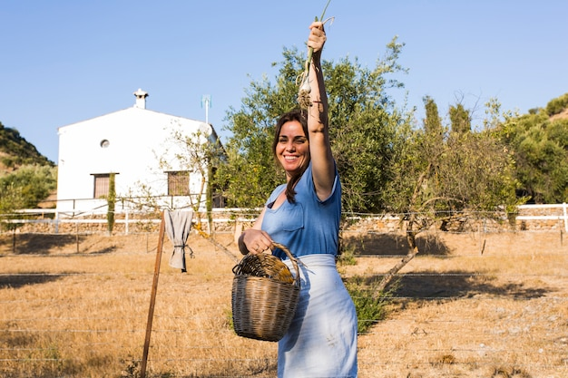 Excited woman showing harvested spring onion in the field