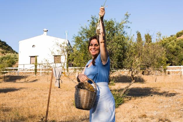 Возбужденная женщина показывает собранный лук весной в поле