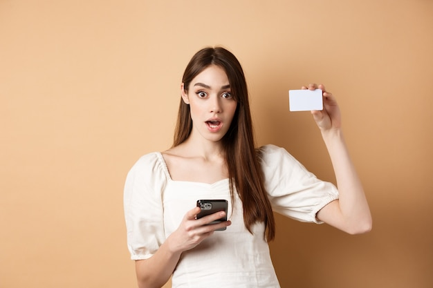 Excited woman showing plastic credit card and using mobile phone app drop jaw and gasping amazed che...