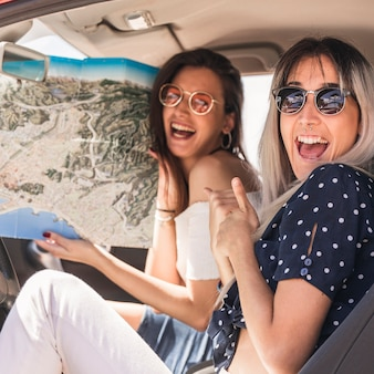 Excited woman sitting beside her friend holding map in the car