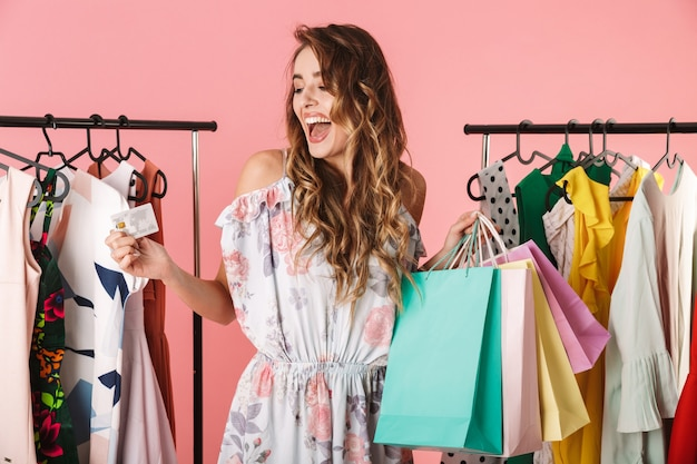 Excited woman standing near wardrobe while holding colorful shopping bags and credit card isolated on pink