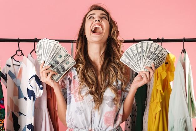Возбужденная женщина, стоящая возле шкафа, держа в руках денежные вентиляторы, изолированные на розовом