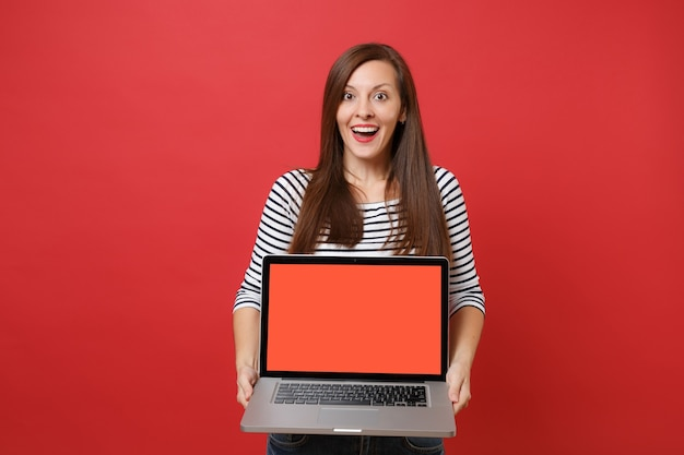 Excited woman in striped clothes looking surprised, holding laptop pc computer with blank black empty screen isolated on red background. people sincere emotions, lifestyle concept. mock up copy space.