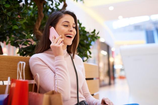 쇼핑몰에서 휴대폰으로 통화하는 흥분된 여성