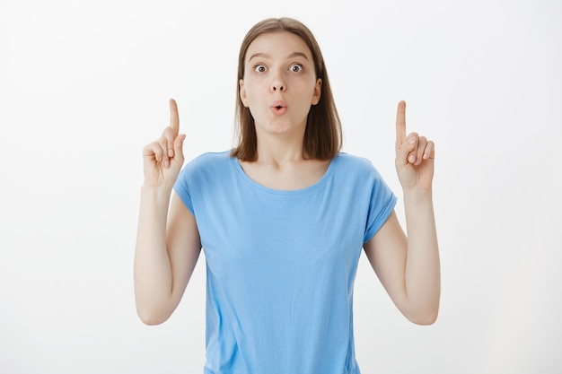 Excited woman tell big news, pointing fingers up making announcement