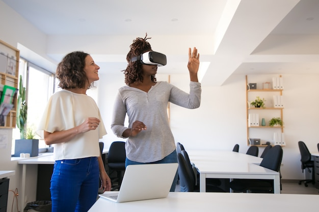 Excited woman testing vr headset with assistant