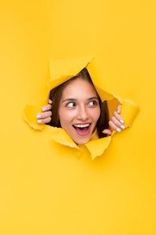 破れた紙の穴から興奮した女性