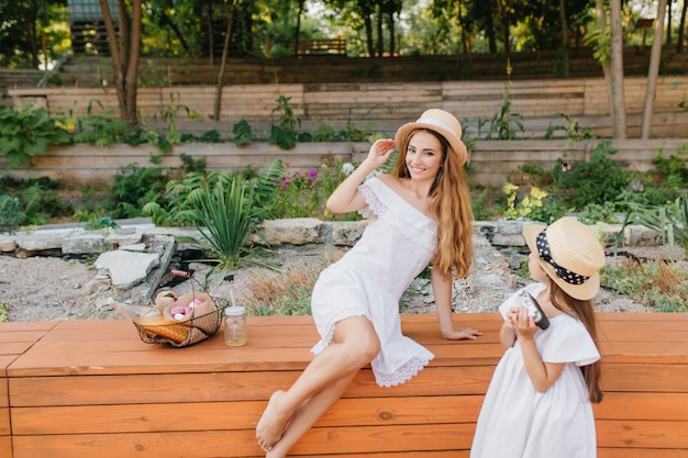 Excited woman in vintage hat posing on nature while her daughter looks at her with interest. outdoor portrait from back of little girl in white dress standing beside flowerbed with mom.