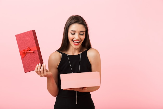 Excited woman wearing black dress holding opened gift box isolated over pink background