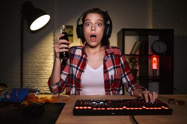 Возбужденная женщина в наушниках играет в онлайн-игры на компьютере и ест закуски