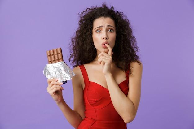 Возбужденная женщина в красном платье держит плитку шоколада, стоя изолированно над фиолетовой стеной