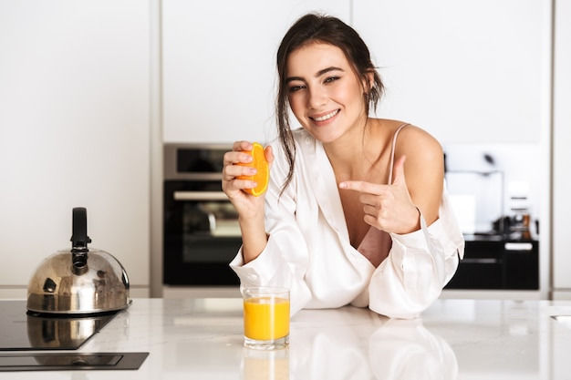 Excited woman wearing silk clothing making fresh juice with orange, during breakfast in kitchen at home