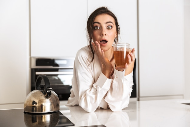 Excited woman wearing silk clothing wondering, while drinking tea in kitchen at home