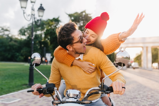 Excited woman wears colorful hat embracing man while he drives scooter