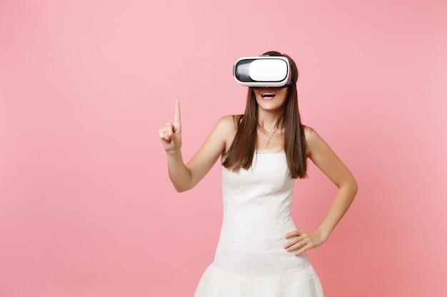Donna eccitata in abito bianco, auricolare della realtà virtuale tocca qualcosa come premere il pulsante o puntare allo schermo virtuale mobile