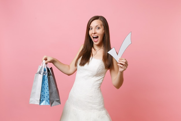 Excited woman in white dress holding check mark, multi colored packages bags with purchases after shopping