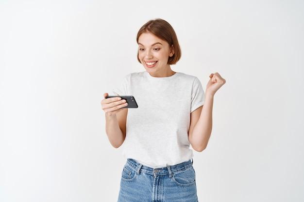 興奮した女性がスマートフォンでビデオゲームに勝ち、スマートフォンの画面を見て幸せそうに言って、白い壁に立って、勝利を祝うためにガッツポーズ