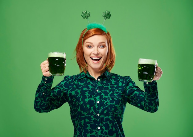 Excited woman with beer making a toast