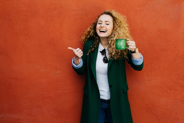 Excited woman with curly blonde hair wearing jacket holding green cup of coffee raising her thumb.