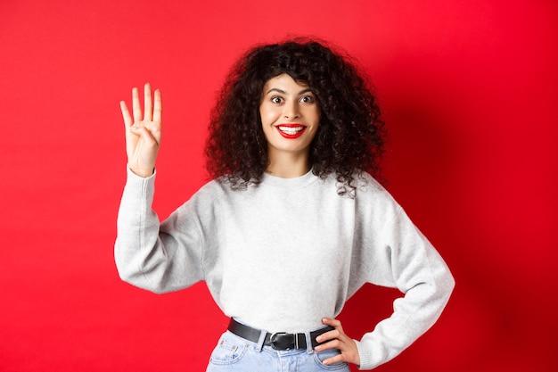 巻き毛の興奮した女性は、指で4番を示し、秩序を作り、赤い背景に立っています。