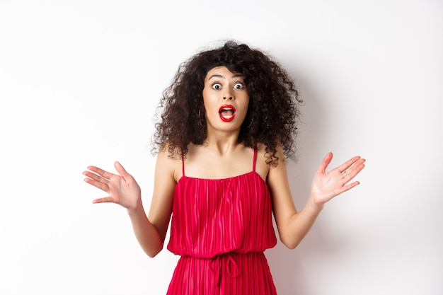 Excited woman with curly hair, talking with amazed face, explain big news, shaking hands and look astonished at camera, white background.