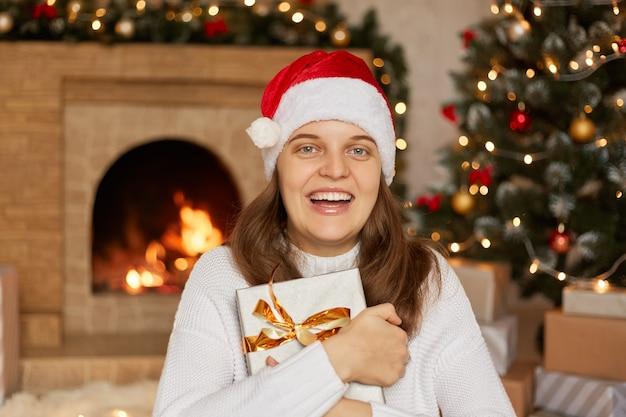 선물 상자를 손에 들고 검은 머리를 가진 흥분된 여자는 산타 모자와 흰색 스웨터, 벽난로 및 x-mas 트리를 입고 이빨 미소로 크리스마스 선물을 가지고 있습니다.