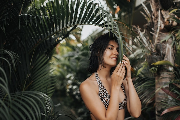 エキゾチックなリゾートでポーズをとる黒髪の興奮した女性。休暇中に楽しんでいる格好良い若い女性。