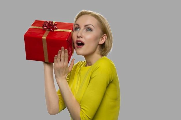 회색 배경에 선물 상자를 가진 흥분된 여자. 선물 상자를 들고 아름 다운 놀된 소녀입니다. 겨울 휴가 축하.