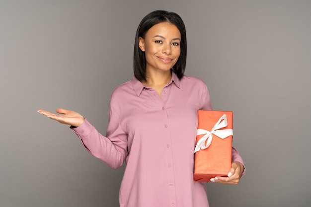 Excited woman with gift box showing sales promotion for seasonal special offers with open hand palm