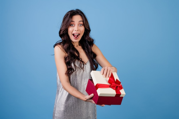 Excited woman with gift box with red ribbon wearing dress isolated over blue