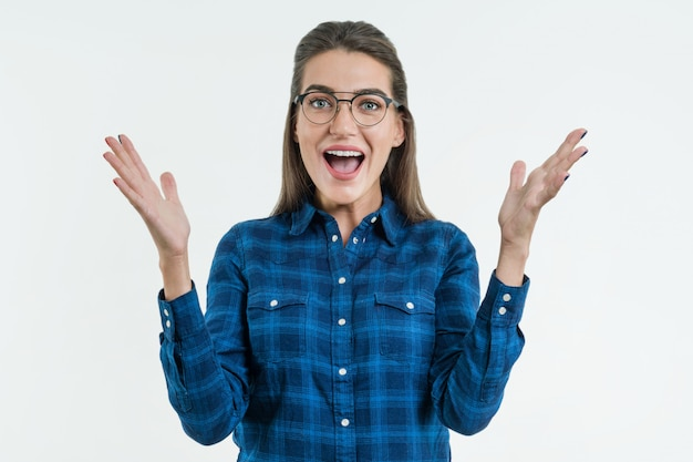 Excited woman with glasses raises hands with enjoyment