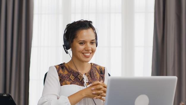 Возбужденная женщина с наушниками во время видеозвонка во время работы из домашнего офиса.