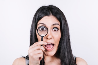 Excited woman with magnifying glass