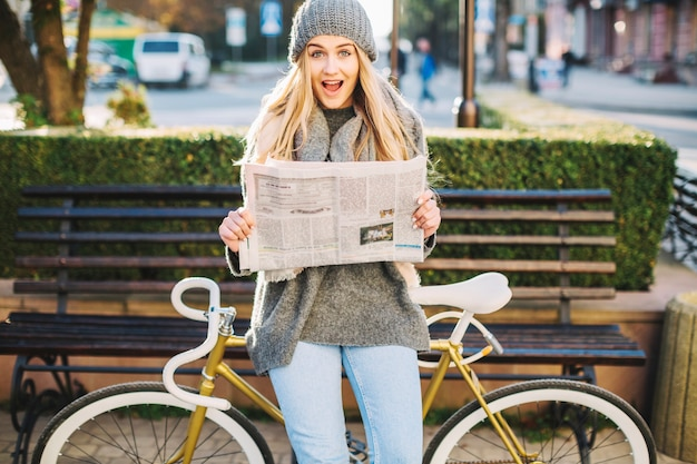 Excited woman with newspaper near bicycle