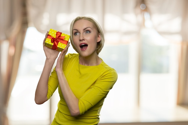 Excited woman with opened mouth holding a small gift box
