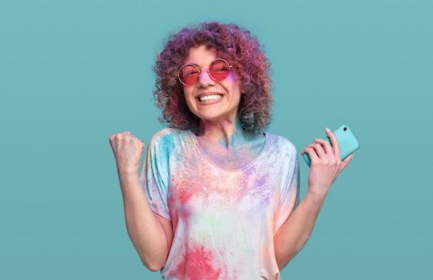 ホーリー祭を楽しむスマートフォンで興奮した女性