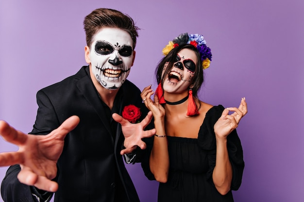 Excited woman in zombie attire joking with boyfriend. positive young people fooling around in halloween.
