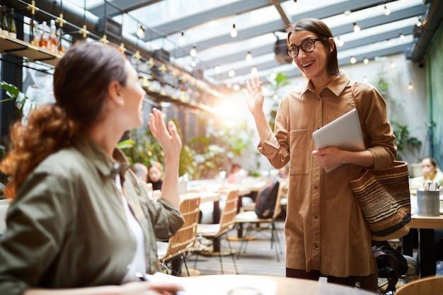 カフェで挨拶する興奮した女性