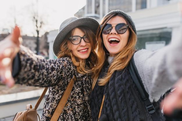 都会を散歩する朝を楽しんでいるスタイリッシュなメガネで興奮した女性。 selfieを作って笑って、手を振ってトレンディな帽子の2人の楽しい友人の屋外のポートレート。